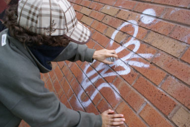Masked youth spraying graffiti